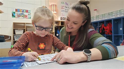 Tiger Paw Early Childhood Center Teacher Vickie Chapman helps student Aria Venables.