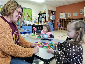 Tiger Paw Teacher Sarah Shivler works with students Claire Nations, right, and Briley Rogers.