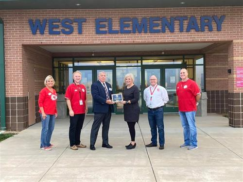 DESE Supervisor Dr. Ron Wilken presents West Elementary with Gold Star plaque